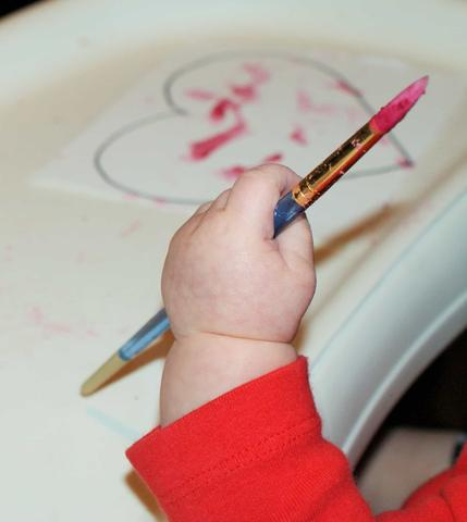 A baby's hand holds a paint brush with red, homemade paint on it