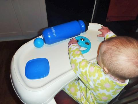 A baby sits in a high chair and plays with blue bells, a blue lid, a blue ball and a blue water container