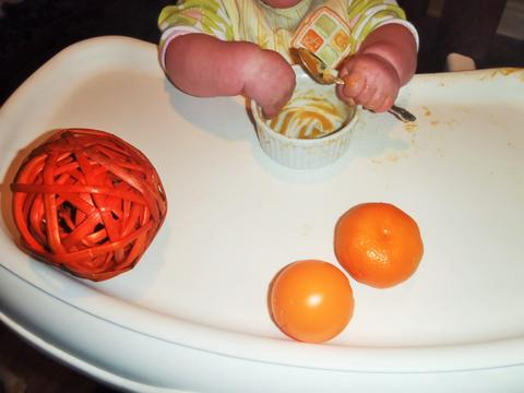 A baby feeds herself orange pureed food and plays with an orange ball, an orange clementine and an orange wicker ball