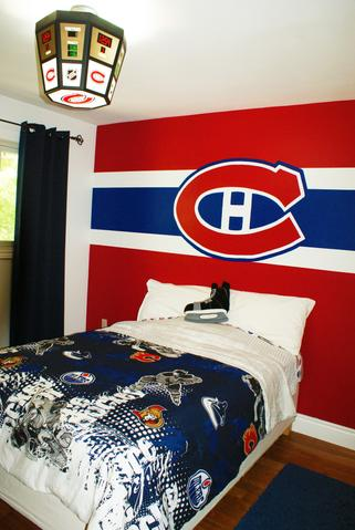 A hand-painted Montreal Canadiens wall mural in a boys bedroom, sits behind a bed with a blue hockey comforter.