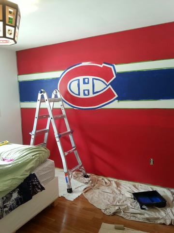 A ladder sits in front of a red, white and blue Montreal Canadiens wall mural