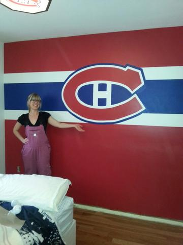 Muralist, Adrienne of AboutMurals.ca, stands next to her red, blue and white Montreal Canadiens mural