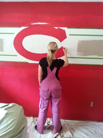"Muralist, Adrienne of AboutMurals.ca, paints a red wall and the letter ""C"" for the Montreal Canadiens wall mural"
