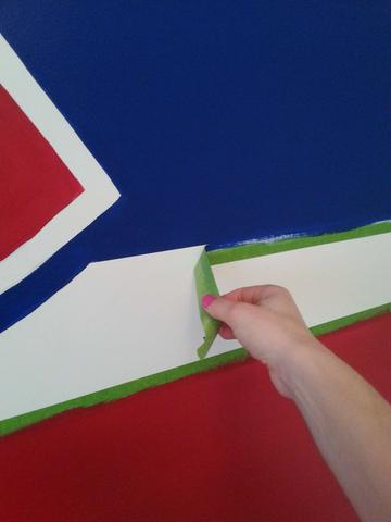 Muralist, Adrienne, pulls painters tape off of a wall mural she painted showing a crisp blue line over white paint