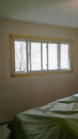 An inside window without trim and a dirty wall are ready to be painted