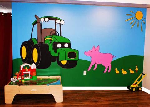 A farm wall mural showing a green John Deere Tractor, a pink pig, 4 yellow ducklings and a sun on blue sky and green grass