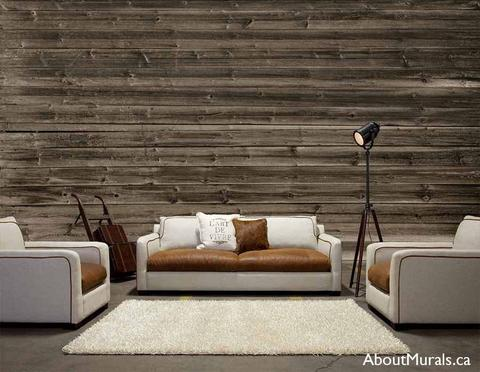 A brown, horizontal barn wood wall mural is on the wall behind a couch, two chairs and a lamp