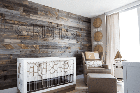 A baby's nursery with a reclaimed wood wall behind a white crib and chair