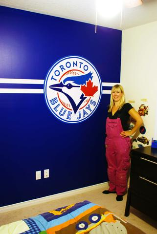 Adrienne from AboutMurals.ca standings in front of her hand-painted Toronto Blue Jays mural with its crisp, white horizontal stripes