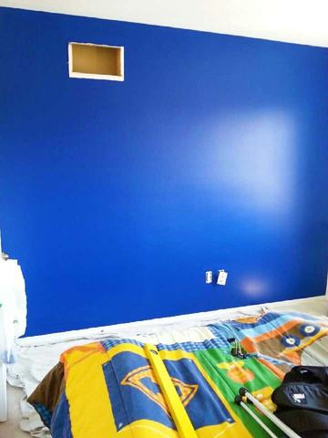 Painted blue wall ready to have stripes painted on it