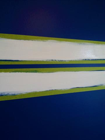 White paint is painted between green painter's tape over blue walls, creating two horizontal white stripes