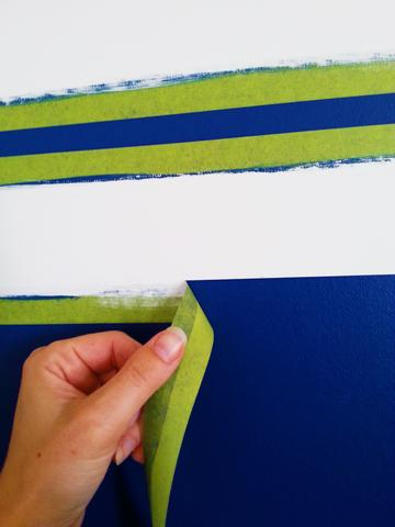 A woman's hand peels painter's tape off a blue wall showing a perfectly crisp painted white horizontal stipe