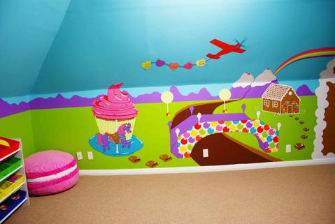 A mural of a candy world including a cupcake carousel, chocolate stepping stones, bubble gum bridge over a chocolate river, an airplane pulling a sweetart banner, ice cream mountains and a gingerbread house