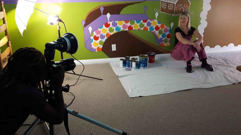 A photographer snaps a photo of muralist, Adrienne of AboutMurals.ca, in front of the candy world wall mural she painted