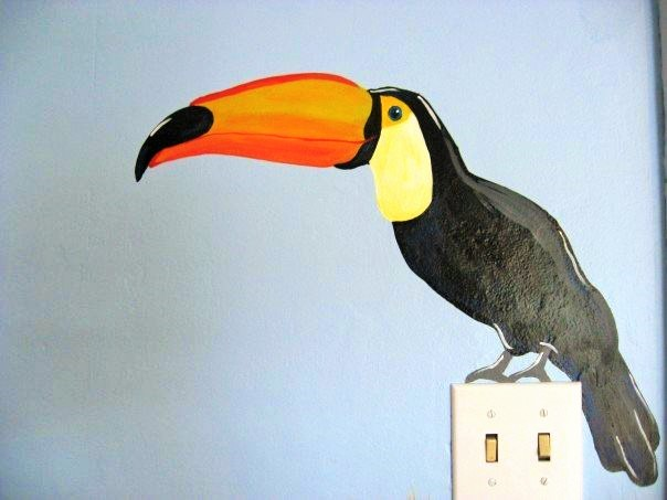 A jungle mural featuring a toucan sitting on a light switch, painted by Adrienne of AboutMurals.ca