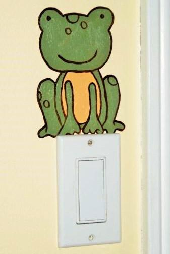 A rainforest mural featuring a frog sitting on a light switch, painted by Adrienne of AboutMurals.ca