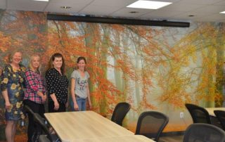 Autumn is Here wall mural is the background to the staff at the Stedman Hospice. Wallpaper sold by AboutMurals.ca