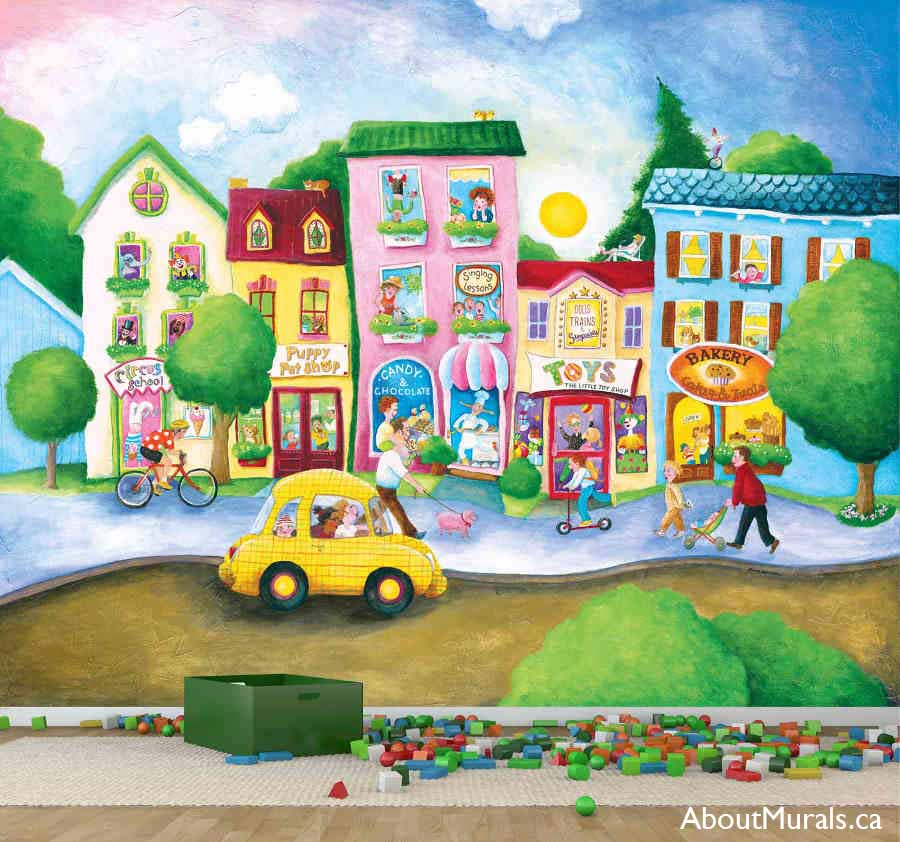 A kids wall mural featuring a street lined with a bakery, candy shop, pet shop and circus school sitting on the wall of a playroom