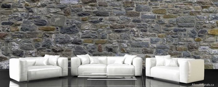 A stone wall mural, sold by AboutMurals.ca, is the backdrop to three white sofas