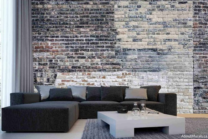 A faux brick wallpaper with black and white decaying paint sits behind a sectional sofa in a living room