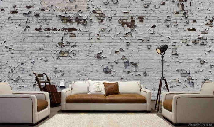 A peeling paint brick wallpaper sits behind a white and brown leather couch in a living room