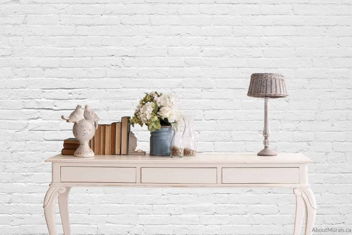A white brick wall mural sold by AboutMurals.ca, behind a side table
