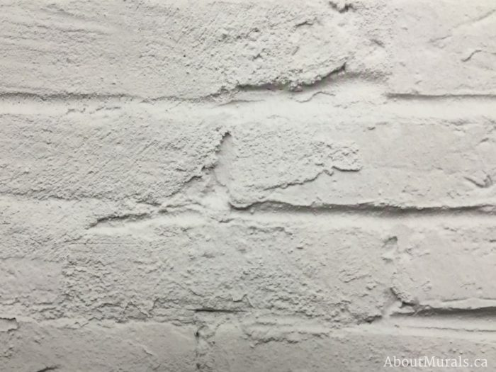 A closeup photo of a white brick wall mural by AboutMurals.ca