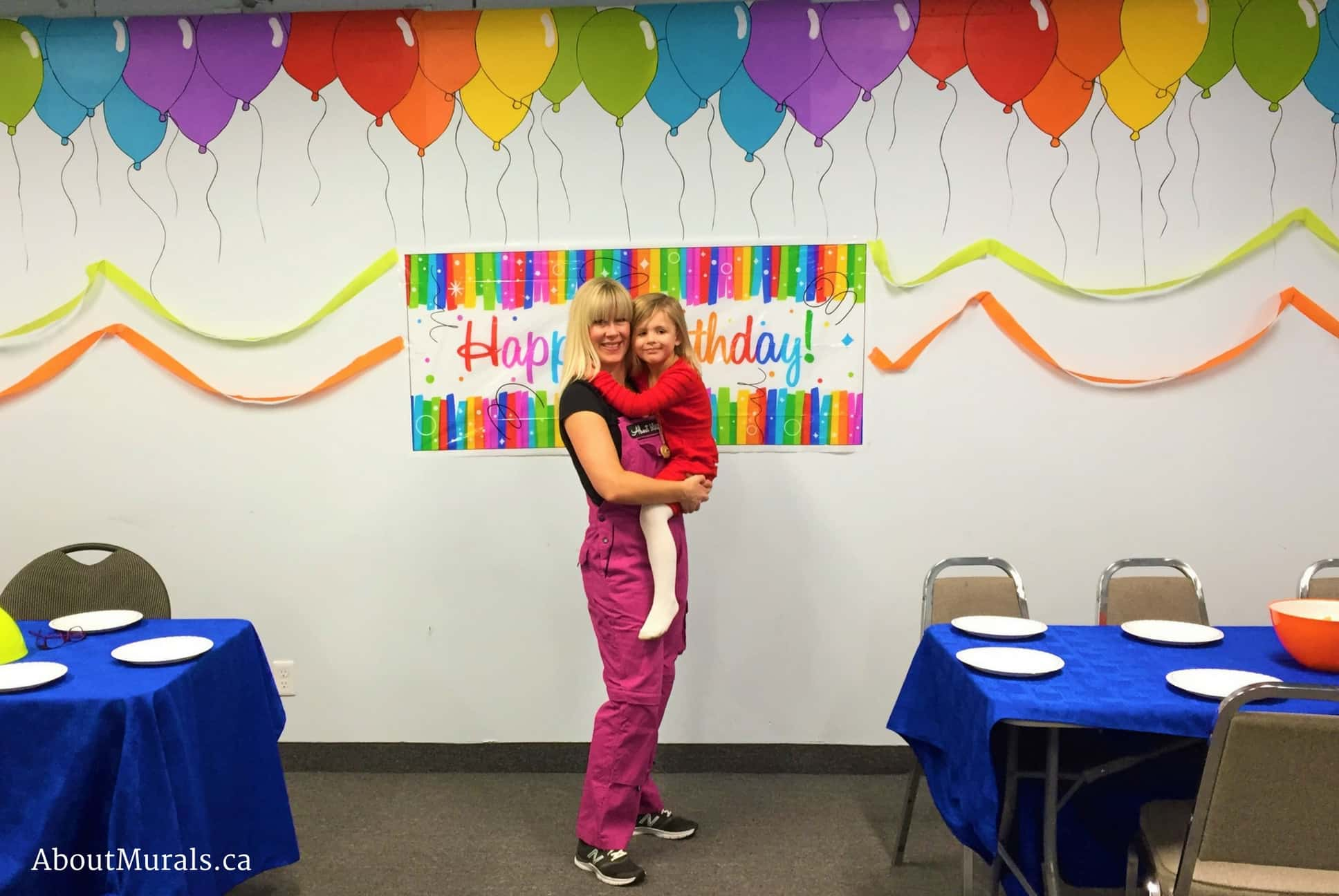 Mural painter Adrienne Scanlan stands under balloons she painted with her daughter