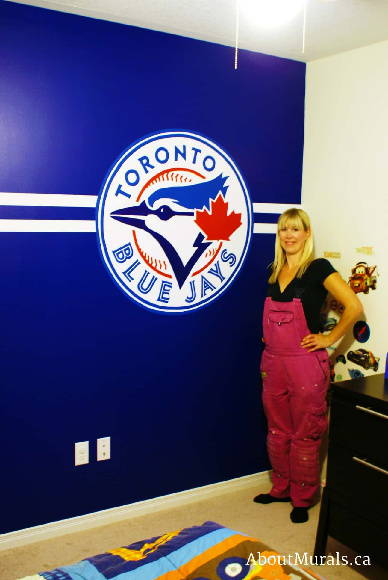 A blue jays wall painted by muralist Adrienne of AboutMurals.ca, who is standing next to the mural
