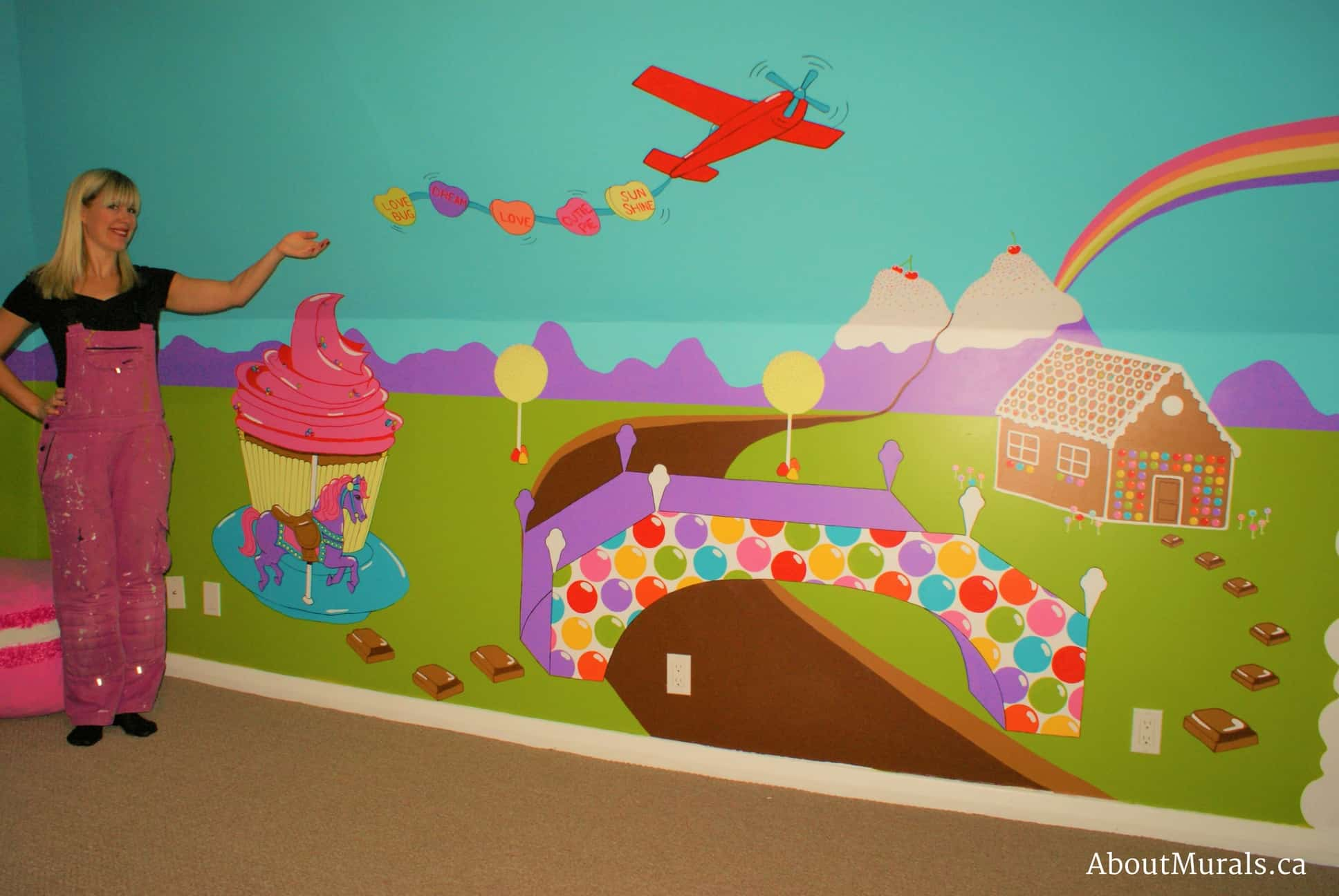 A candy mural, painted by Adrienne of AboutMurals.ca, features a cupcake carousel, a plane totting sweet tart candies, a bubble gum bridge, gingerbread house, ice cream mountains, flowing chocolate river and chocolate stepping stones.