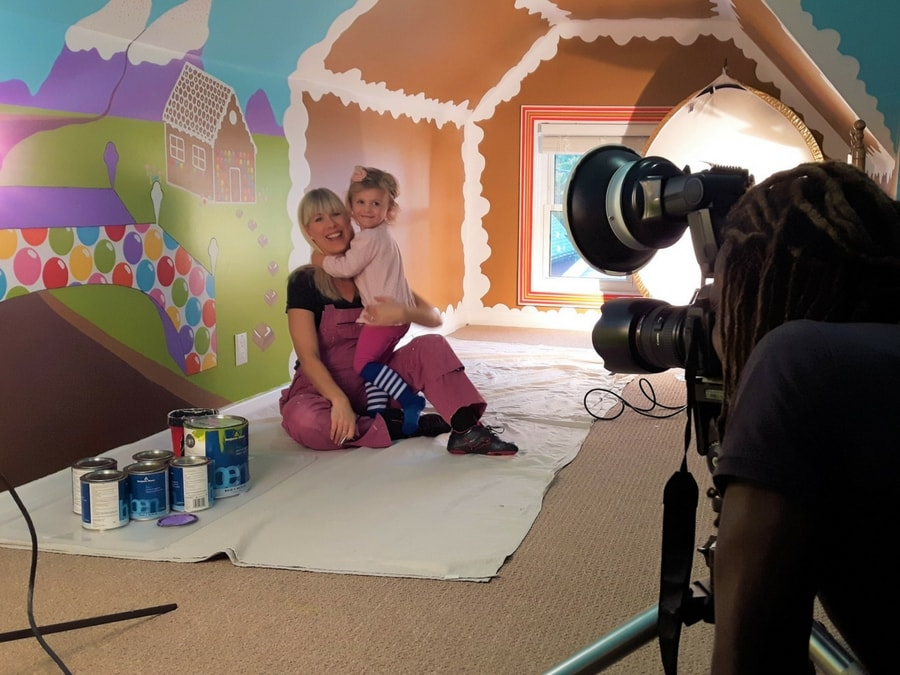 Adrienne Scanlan sits in front of her Candy World Mural with daughter in front of photographer