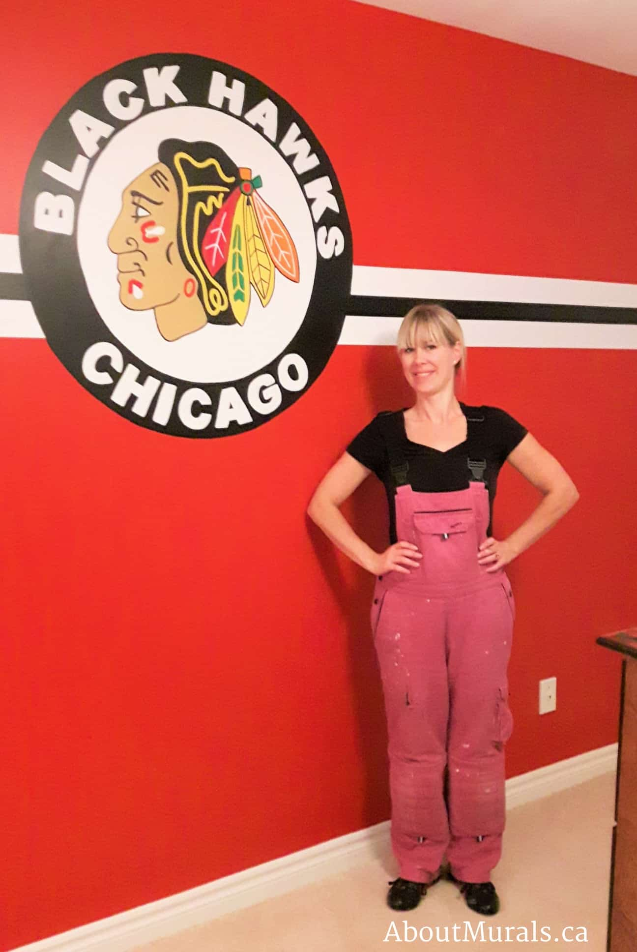 Muralist Adrienne Scanlan stands next to a Chicago Blackhawks logo she painted