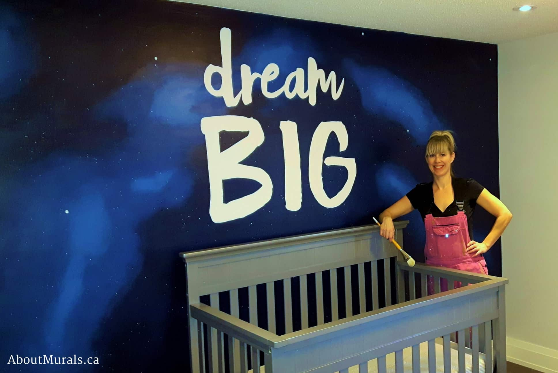 Mural painter Adrienne Scanlan stands next to a kids wall mural featuring the words Dream Big painted over an outer space sky