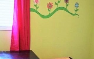 A kid wall mural featuring a border of flowers painted around a window
