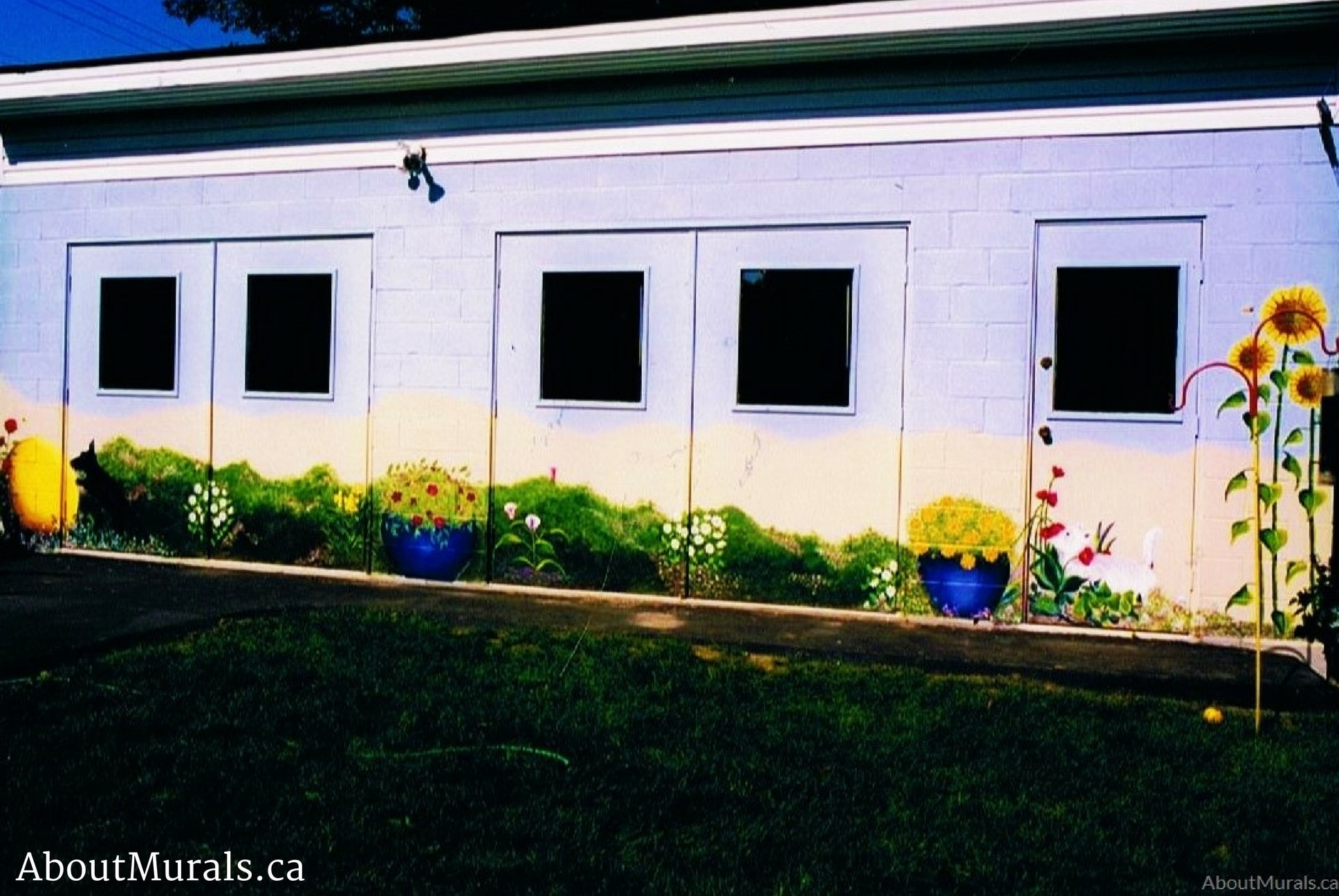 A garden mural painted on a garage featuring sunflowers, roses, petunias and two dogs