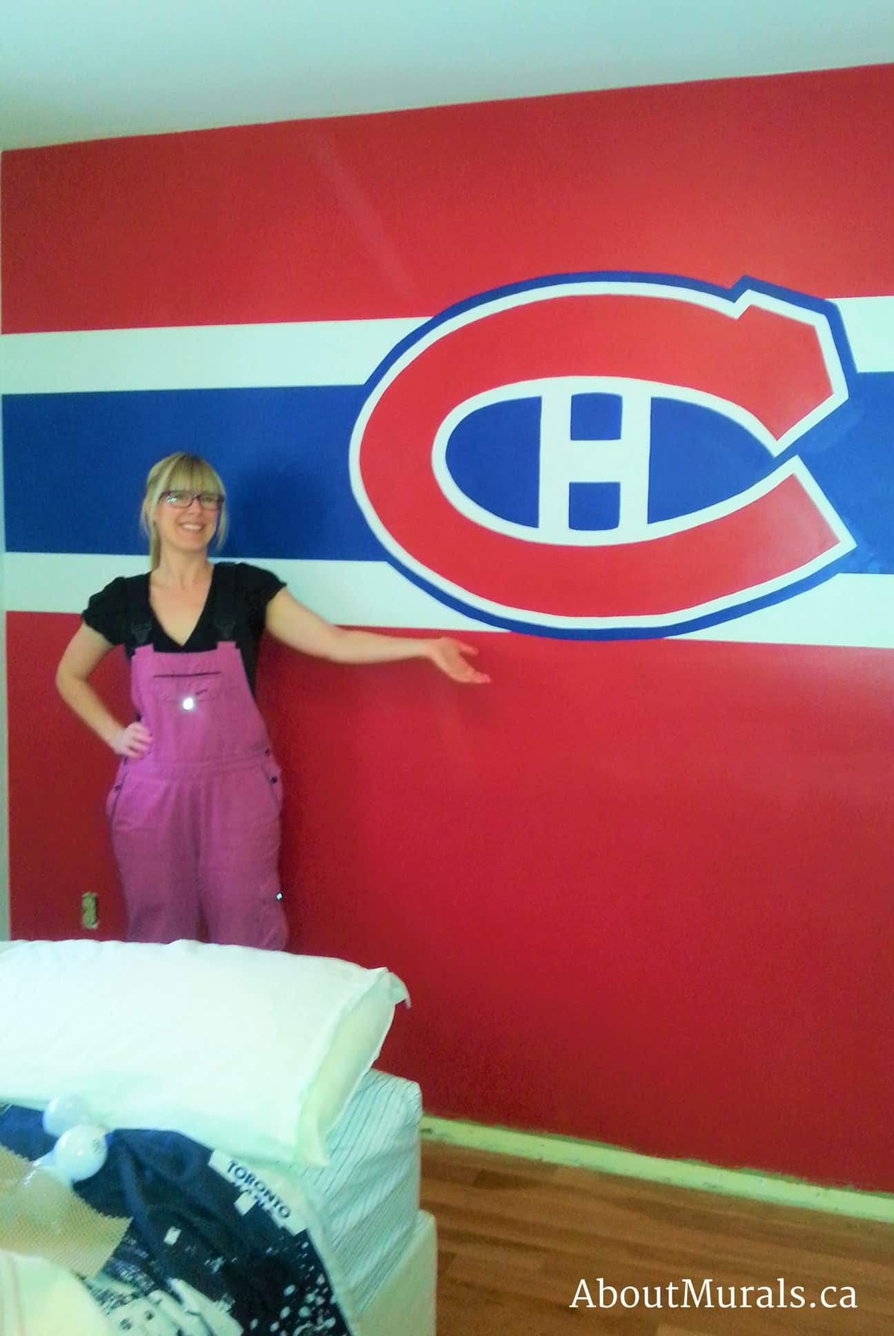 Muralist Adrienne Scanlan stands next to a Montreal Canadiens mural she painted