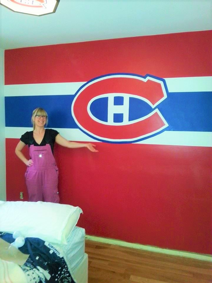 Muralist Adrienne stands next to the Montreal Canadiens mural she painted