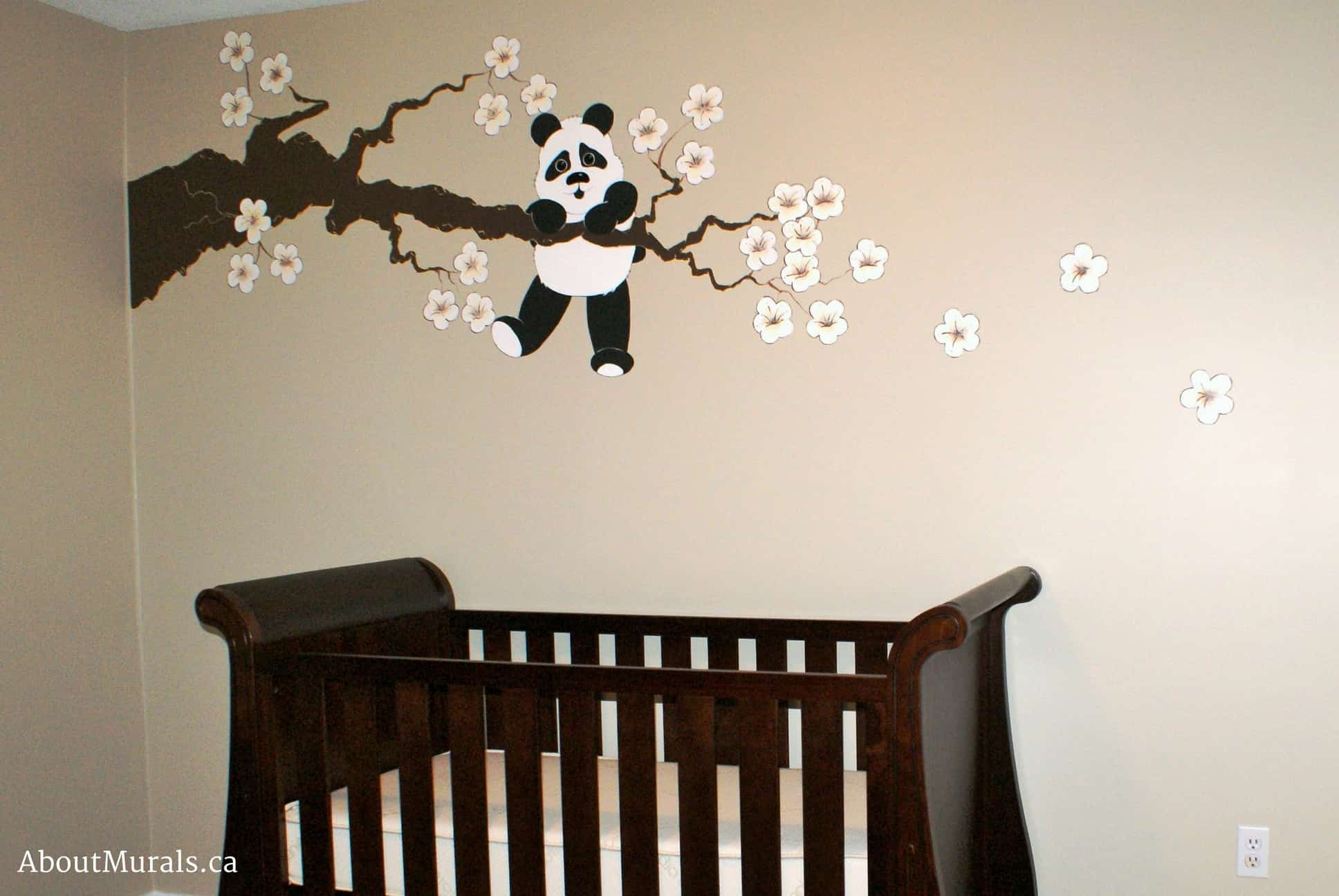 A kids wall mural featuring a panda hanging on to a cherry blossom tree over a baby crib