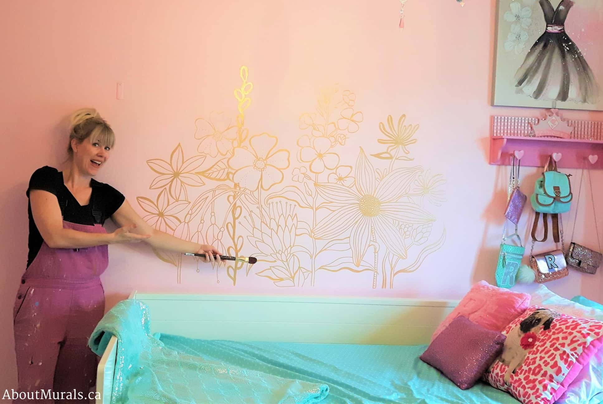 Mural painter Adrienne Scanlan stands beside a kids wall mural featuring flowers painted in gold on a pink wall