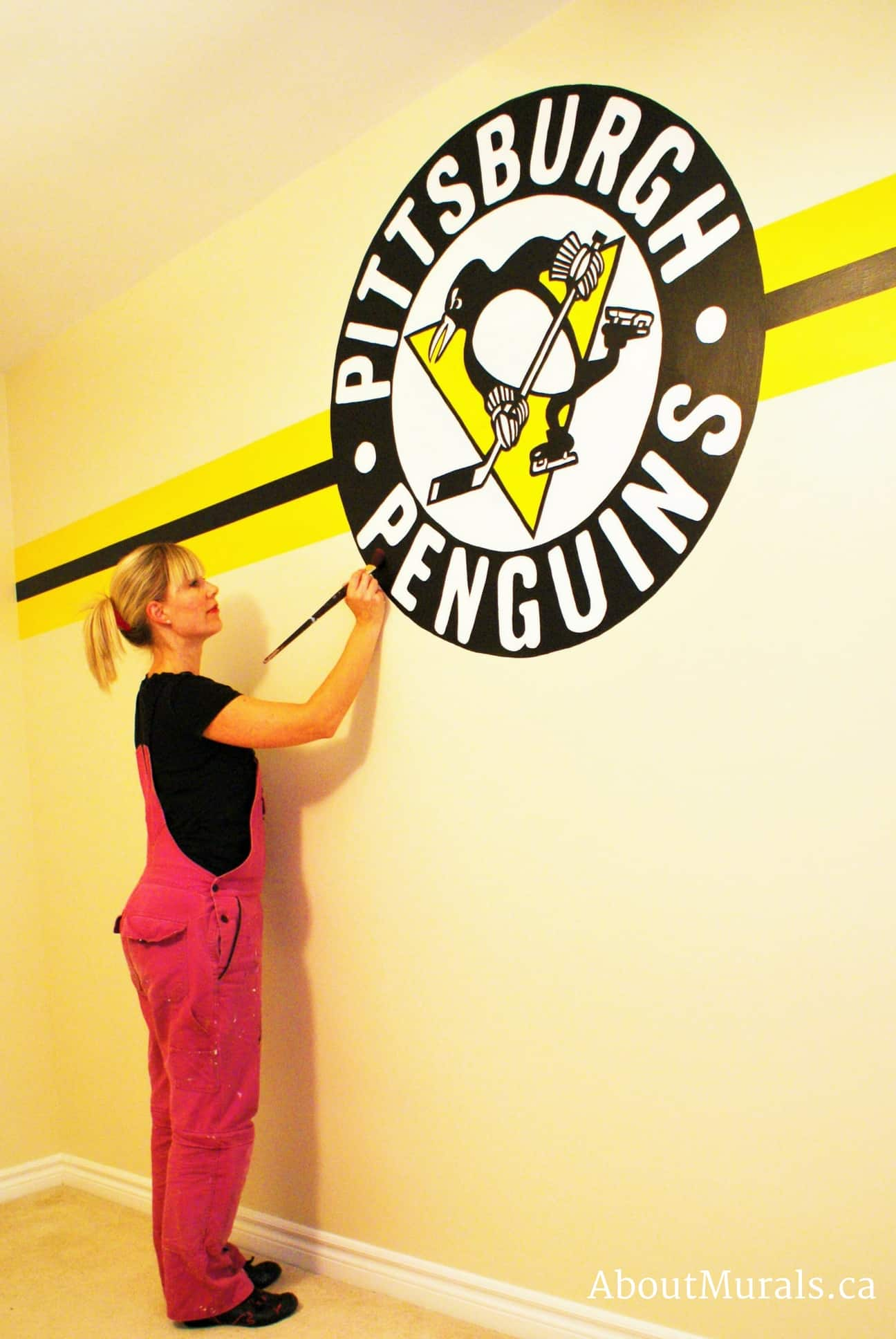 Muralist Adrienne Scanlan paints a Pittsburgh Penguins logo