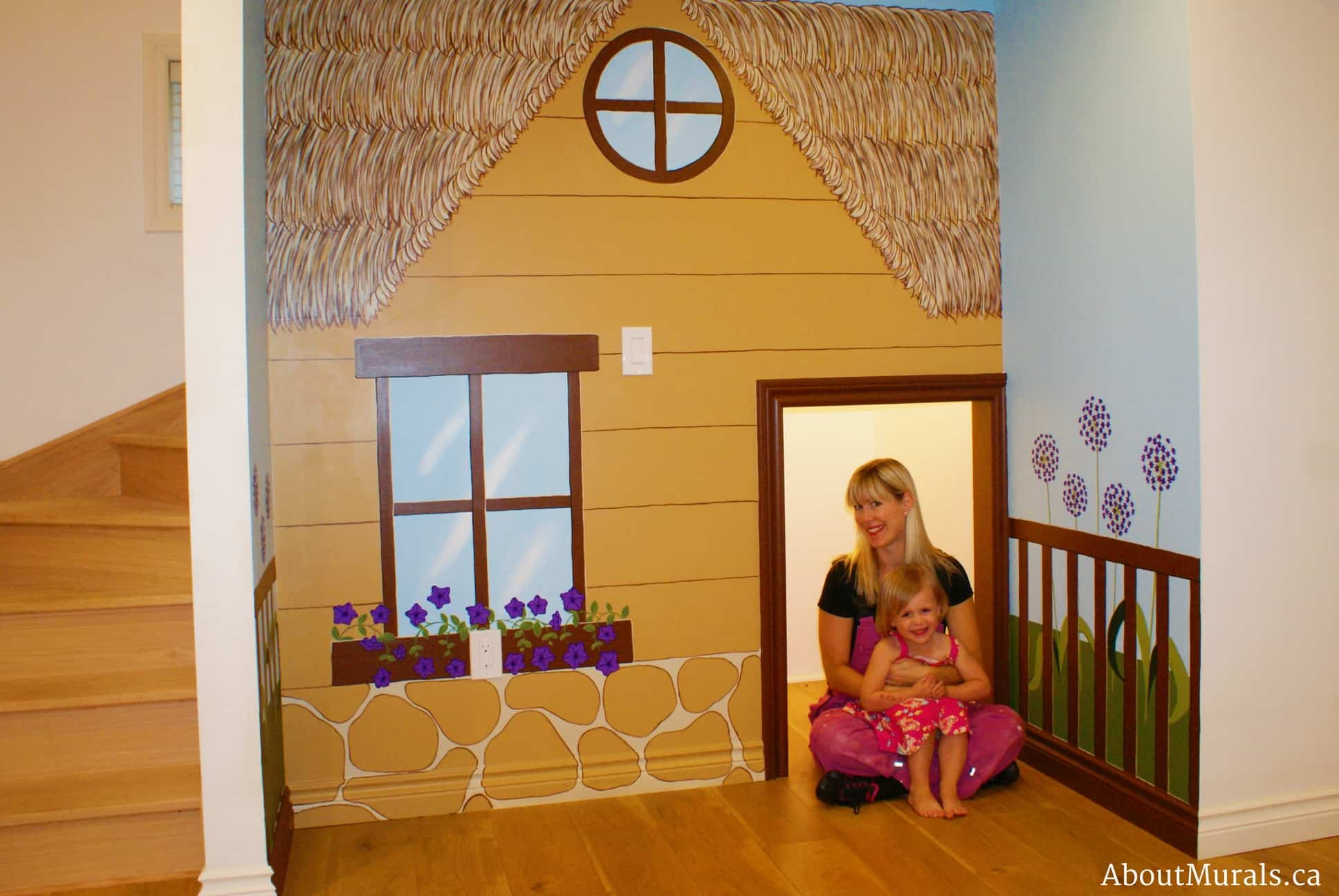 Mural painter Adrienne Scanlan sits in the doorway of a playhouse mural she painted