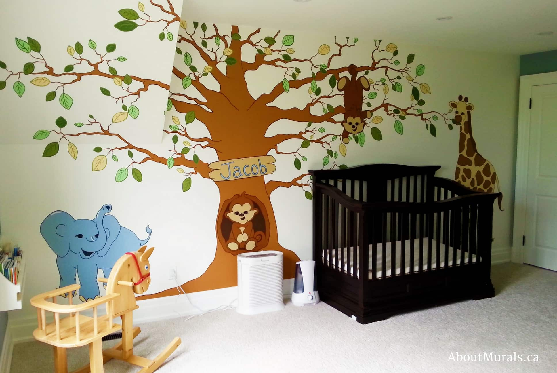A safari tree mural featuring a tree with an elephant, giraffe and monkeys over a baby crib