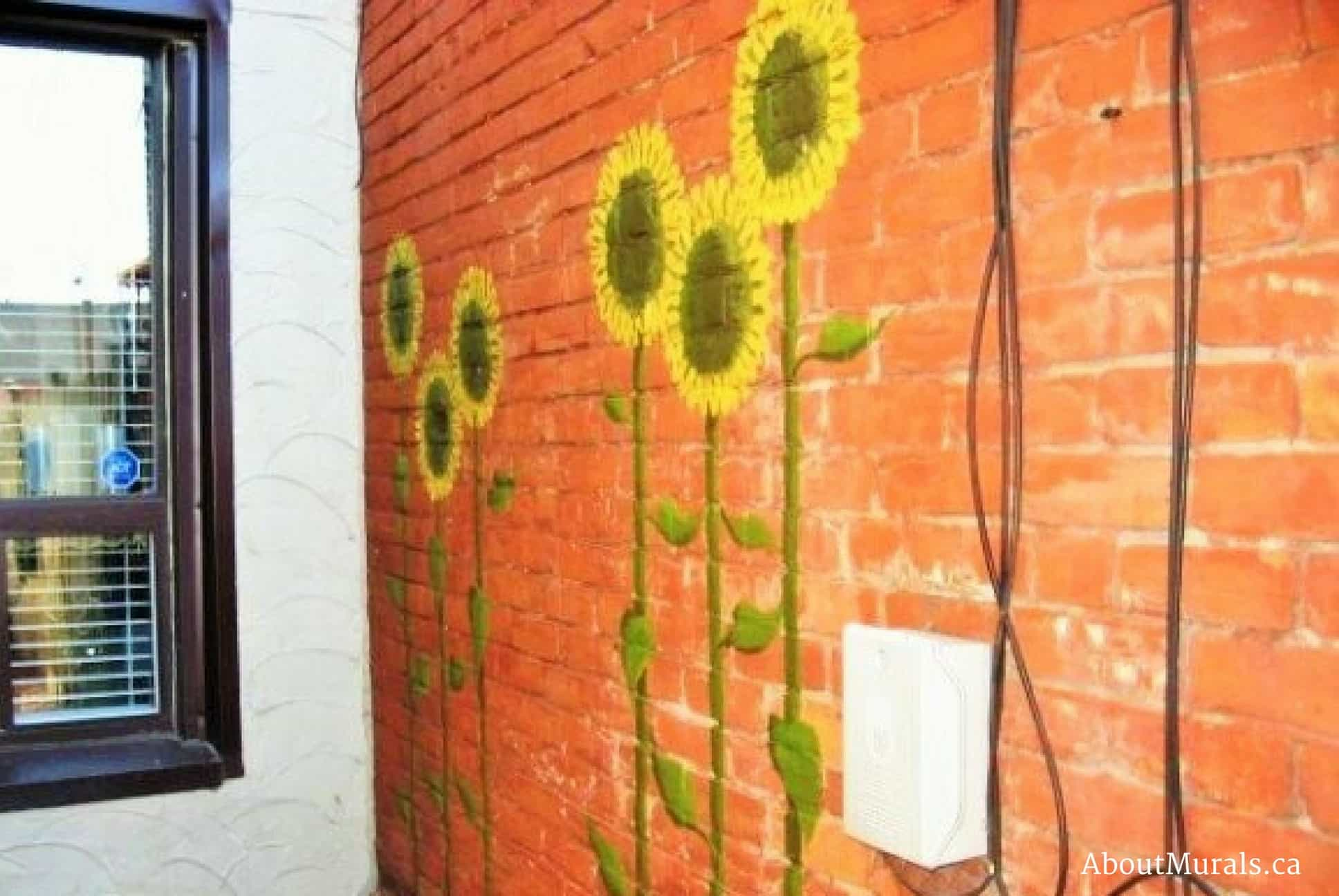 A flower mural featuring sunflowers painted on the side of a brick home