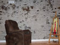 An industrial brick wallpaper sits behind a brown leather chair and an artist easel