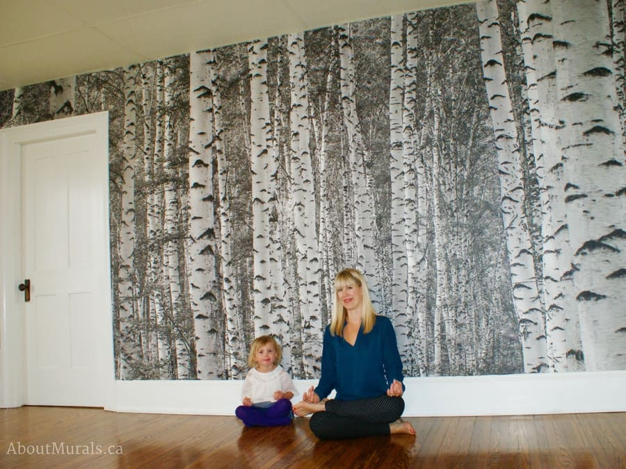 A birch tree wallpaper in black and white is the background to AboutMurals.ca owner Adrienne and her daughter Audrey doing a yoga pose in a yoga studio