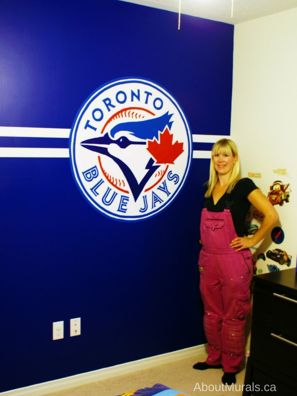Muralist, Adrienne of AboutMurals.ca, stands next to a baseball mural she painted of a Toronto Blue Jays logo