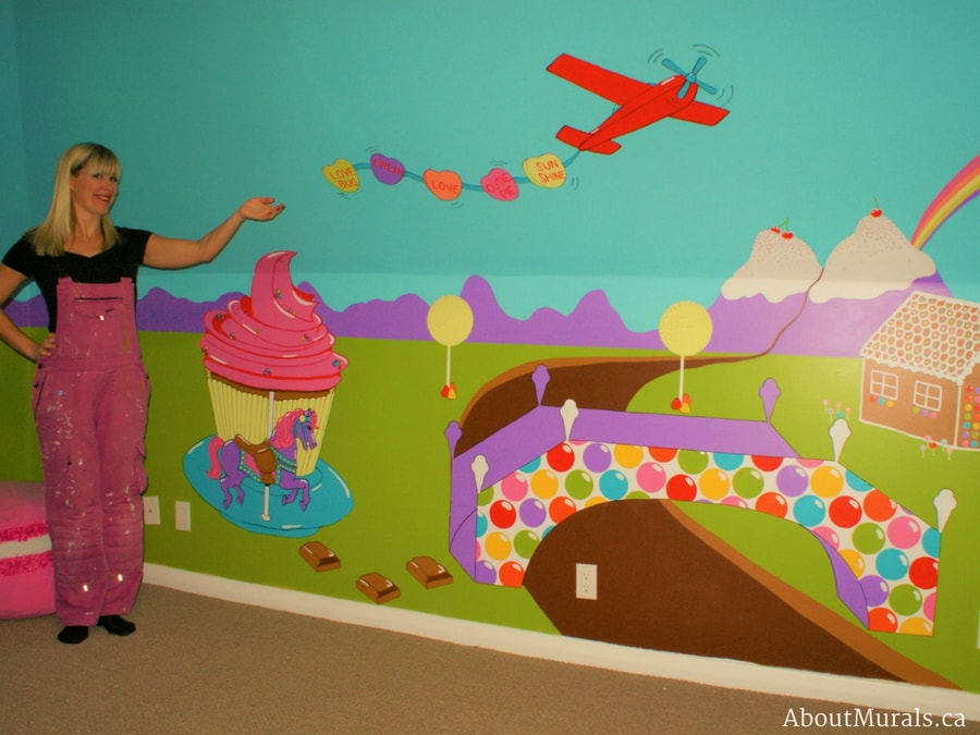 A candy mural, painted by Adrienne of AboutMurals.ca, features a cupcake carousel, airplane totting sweet tart candy, bubble gum bridge, ice cream mountains, flowing chocolate river and gingerbread house.