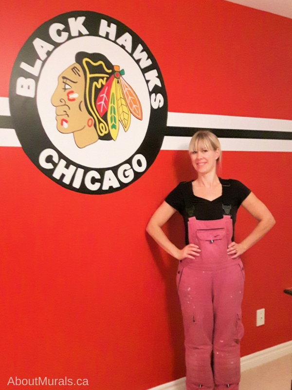 Muralist, Adrienne of AboutMurals.ca, stands next to a Chicago Blackhawks mural she painted
