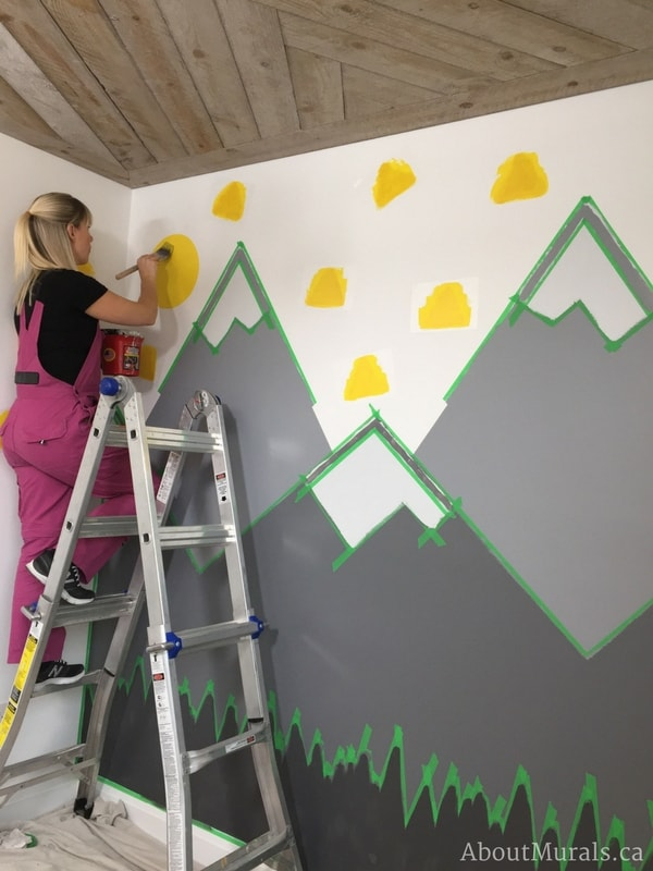 Holmes Next Generation contractor, Adrienne of AboutMurals.ca, paints a yellow sun and triangles in the mountain mural