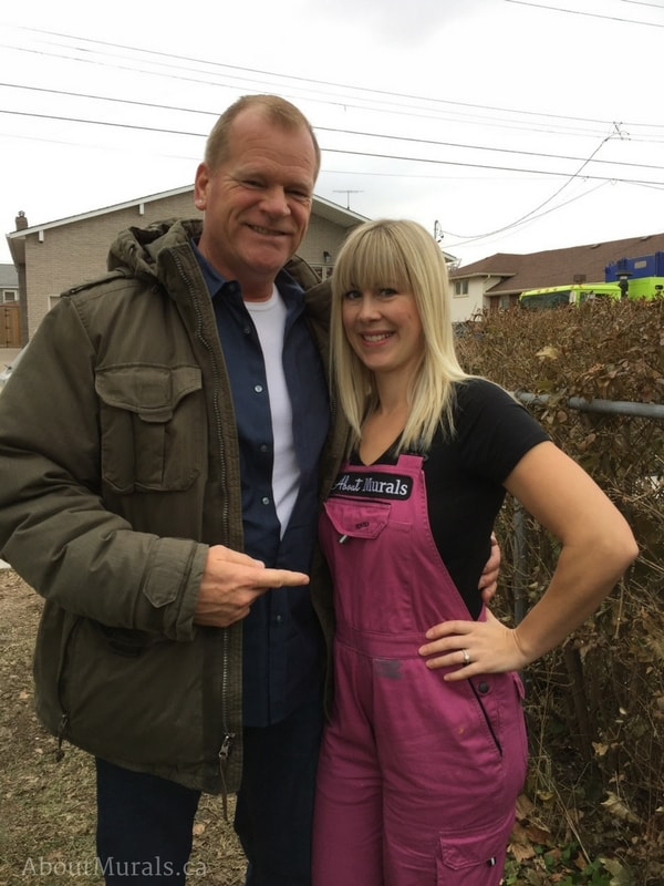 Holmes Next Generation star Mike Holmes stands with Adrienne of AboutMurals.ca after she finished painting a mural for the television show